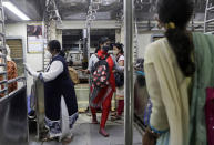 Women passengers enter a local train in Mumbai, India, Wednesday, Oct. 21, 2020. Indian railways has permitted women passengers to travel in local trains during non-peak hours beginning Wednesday, which otherwise has been running only for essential services. (AP Photo/Rajanish Kakade)