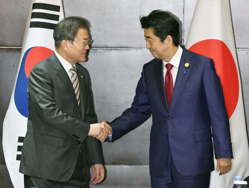 Japan's Prime Minister Shinzo Abe shakes hands with South Korea's President Moon Jae-in during their meeting in Chengdu, China