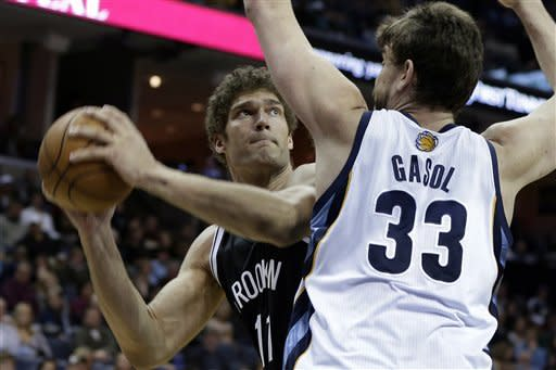 Brooklyn Nets' Brook Lopez (11) looks for room around Memphis Grizzlies' Marc Gasol, of Spain, during the first half of an NBA basketball game in Memphis, Tenn., Friday, Jan. 25, 2013. (AP Photo/Danny Johnston)