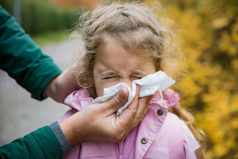 Father wiping daughter's nose with handkerchief. Sick little girl with cold and flu standing outdoors. Preschooler sneezing, coughing, having runny red nose. Autumn street background