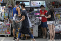 People buy Apple Daily at a downtown street in Hong Kong Friday, June 18, 2021. The pro-democracy paper increased its print run to 500,000 copies on Friday, a day after police arrested five top editors and executives and froze $2.3 million in assets linked to the media company. (AP Photo/Vincent Yu)