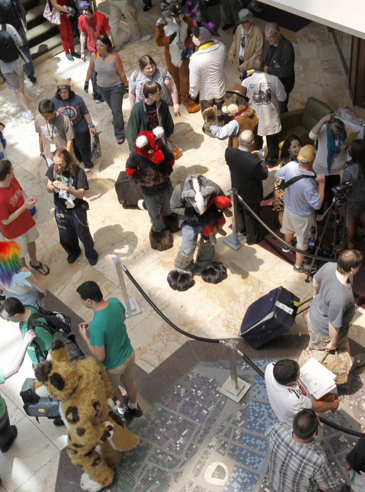 In this photo made on Thursday, June 14, 2012, people attending Anthrocon, some in animal costumes, greet and mingle in the lobby of the Westin Convention Center hotel in Pittsburgh. Anthrocon, the world's largest convention for people who dress and assume the rolls of fictional animal characters, is back in its adopted home with an expected 5,000 participants between June 14 to 17, 2012. (AP Photo/Keith Srakocic)
