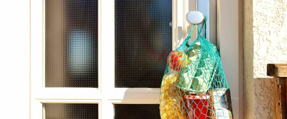 Shopping bag with Merchandise, goods and food is hanging at the front door