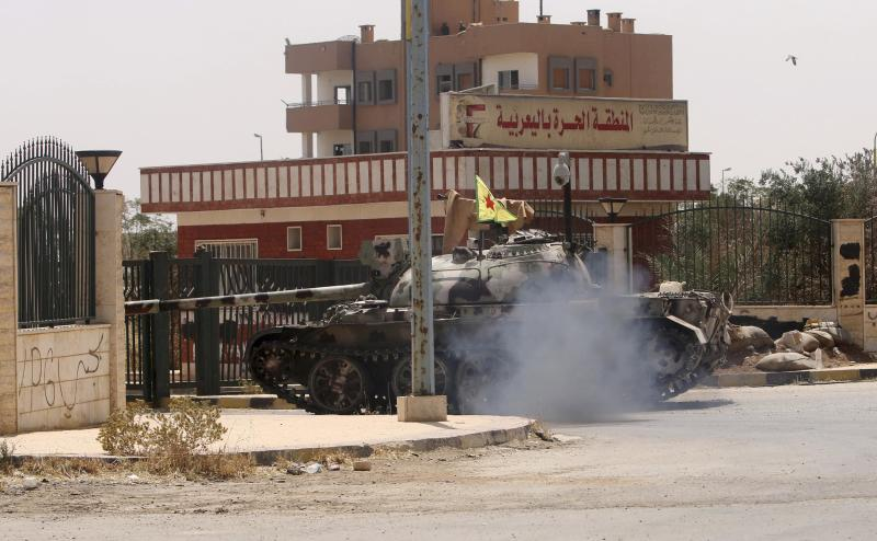 A Kurdish People's Protection Units tank is driven during clashes with forces loyal to the Islamic State in the Syrian-Iraqi border town of Elierbeh of al-Hasakah Governorate