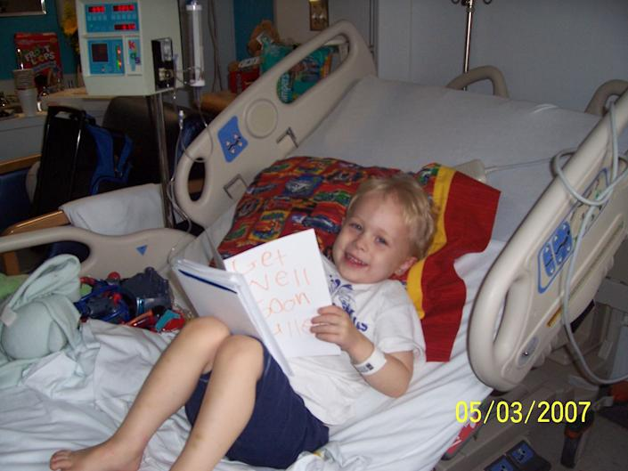 Fuller smiles in his hospital bed and reads a get well soon card shortly after he was diagnosed with cancer (Photo courtesy of Melissa Goldsmith)