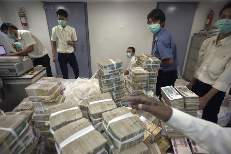 Employees count and pack money inside a bank in Yangon