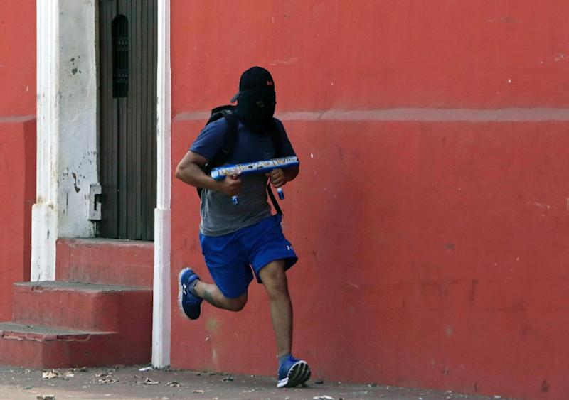A demonstrator runs carrying a homemade mortar during protests in Masaya, near Managua (AFP Photo/INTI OCON)