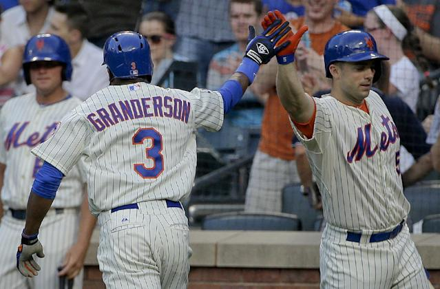 New York Mets right fielder Curtis Granderson (3) is greeted by New York Mets' David Wright (5) after hitting a solo home run against the Atlanta Braves during the first inning of a baseball game, Tuesday, July 8, 2014, in New York. (AP Photo/Julie Jacobson)