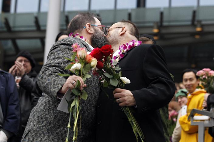 Liam, right, and Richard Sauer-Wooden kiss on the steps of Seattle City Hall after getting married, Sunday, Dec. 9, 2012, in Seattle. Gov. Chris Gregoire signed a voter-approved law legalizing gay marriage Wednesday, Dec. 5 and weddings for gay and lesbian couples began in Washington on Sunday, following the three-day waiting period after marriage licenses were issued earlier in the week. (AP Photo/Elaine Thompson)