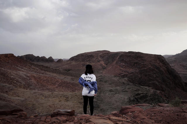 In this March 29, 2019 photo, a Korean tourist poses for a photograph for her friend on a trek in the mountains near Wadi Sahw, Abu Zenima, in South Sinai, Egypt. Four Bedouin women are for the first time leading tours in Egypt's Sinai Peninsula, breaking new ground in their deeply conservative community, where women almost never work outside the home or interact with outsiders. (AP Photo/Nariman El-Mofty)