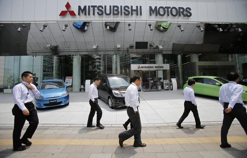 Men walk in front of Mitsubishi Motors Corp's headquarters in Tokyo