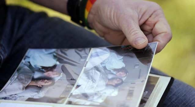 Rob Robertson, who wears a gay pride rainbow wristband, pages through a photo album of the final days of his son, Ryan, in Issaquah, Washington. Photo: AP