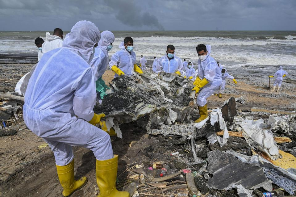 Sri Lankan Navy soldiers work to remove debris washed ashore from the Singapore-registered container ship MV X-Press Pearl, which has been burning for the eighth consecutive day in the sea off Sri Lanka's Colombo Harbour, on a beach in Colombo on May 28, 2021. (Photo by Ishara S. KODIKARA / AFP) (Photo by ISHARA S. KODIKARA/AFP via Getty Images) (AFP via Getty Images)