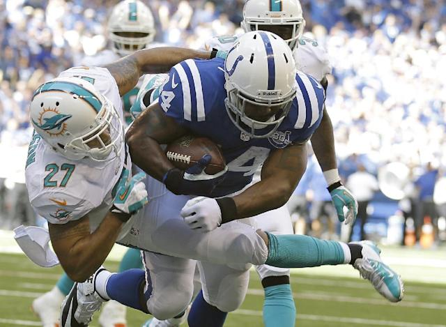 Indianapolis Colts' Ahmad Bradshaw (44) is tackled by Miami Dolphins' Jimmy Wilson (27) during the first half an NFL football game Sunday, Sept. 15, 2013, in Indianapolis. (AP Photo/Michael Conroy)