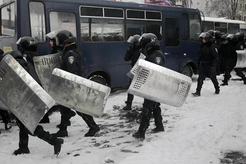 Riot police officers leave their bus to block Pro-European Union activists gathered at the Independence Square in KIev, Ukraine, Monday, Dec. 9, 2013. The policemen, wearing helmets and holding shields, formed a chain across Kiev's main street outside the city building. Organizers called on protesters to vacate the city hall and the other building which the opposition had used as its headquarters. (AP Photo/Sergei Chuzavkov)