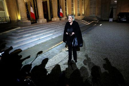 The shadows of journalists are seen as Marine Le Pen, head of France's far-right National Front (FN) speaks to the media following a meeting with French President Emmanuel Macron at the Elysee Palace in Paris