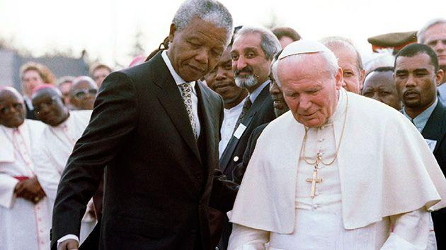South African President Nelson Mandela guides Pope John Paul II after they met at Johannesburg International Airport. Photo: Reuters.