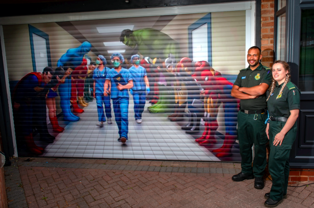 Paramedic Aaron Duncan and technician Kim Haynes look at the artwork paying tribute to NHS workers on Craig Perkins's garage door. (SWNS)