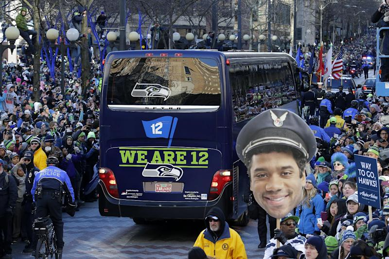 A photo of Seattle Seahawks quarterback Russell Wilson is held up by fans lining the street during the Super Bowl champions parade on Wednesday, Feb. 5, 2014, in Seattle. The Seahawks beat the Denver Broncos 43-8 in NFL football's Super Bowl XLVIII on Sunday. (AP Photo/Ted S. Warren)
