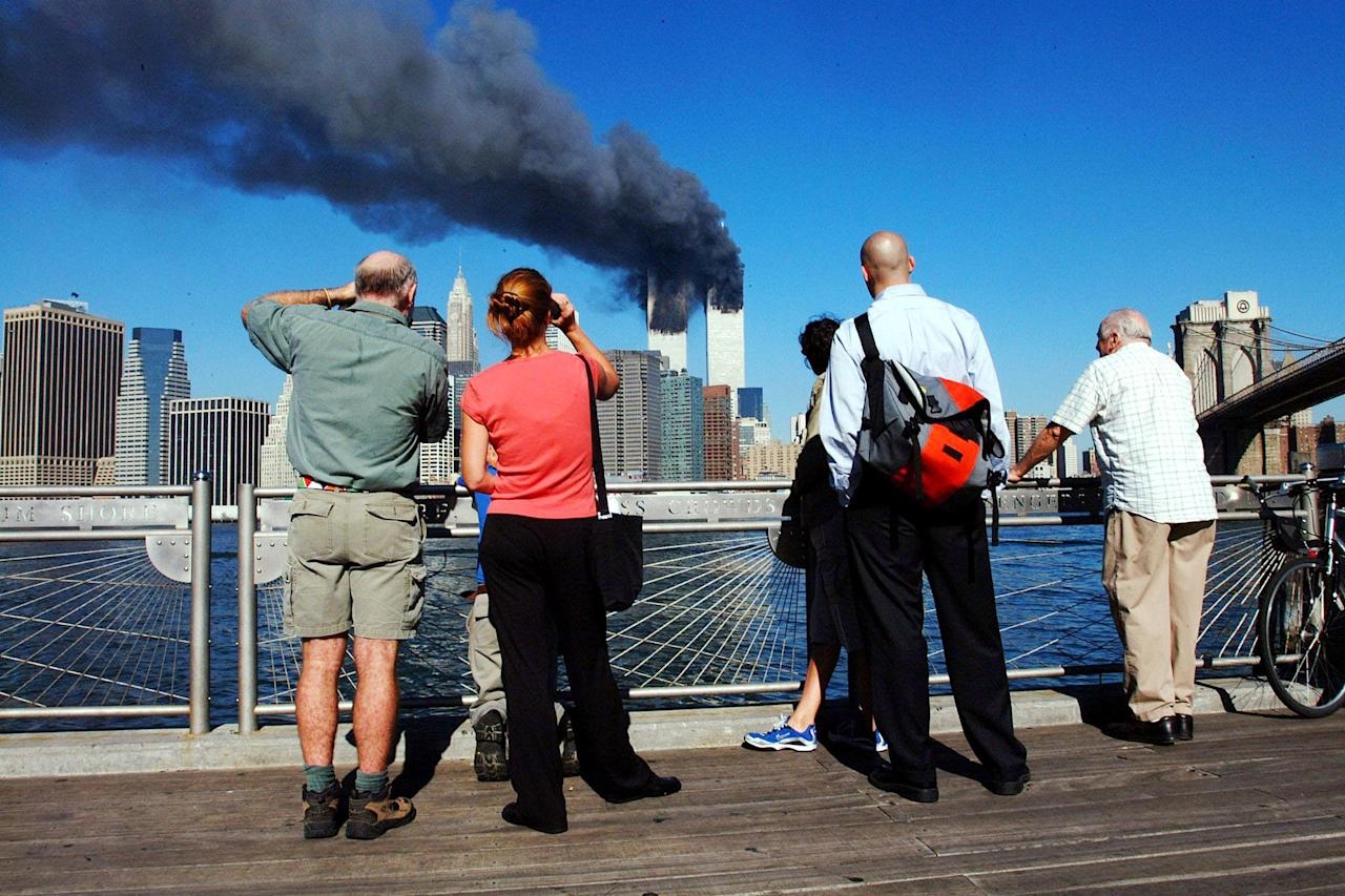<p>Pedestrians on the waterfront in Brooklyn look across the East River to the burning World Trade Center towers on Sept. 11, 2001. (Photo: Henny Ray Abrams/AFP/Getty Images) </p>