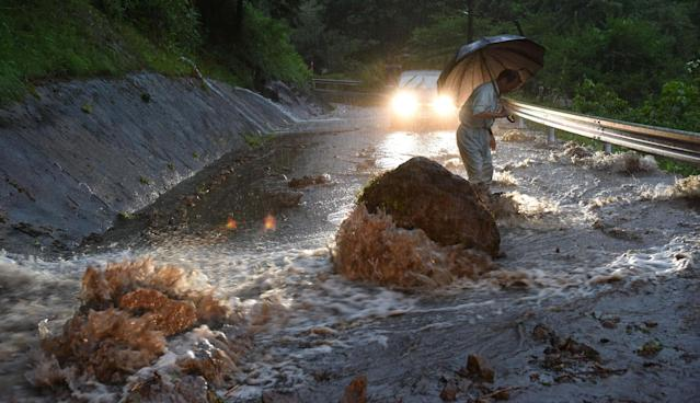 <p>A flooded road with fallen rocks is pictured in Hita in Oita Prefecture, Japan, after torrential rain hits on July 5, 2017. (Photo: Kyodo via Reuters) </p>