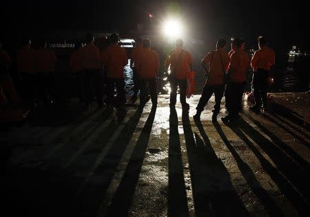 Search and Rescue team members stand by as they get ready to board SAR ship Purworejo for search operations for passengers onboard AirAsia flight QZ8501 at Kumai port, Pangkalan Bun district December 31, 2014. REUTERS/Beawiharta