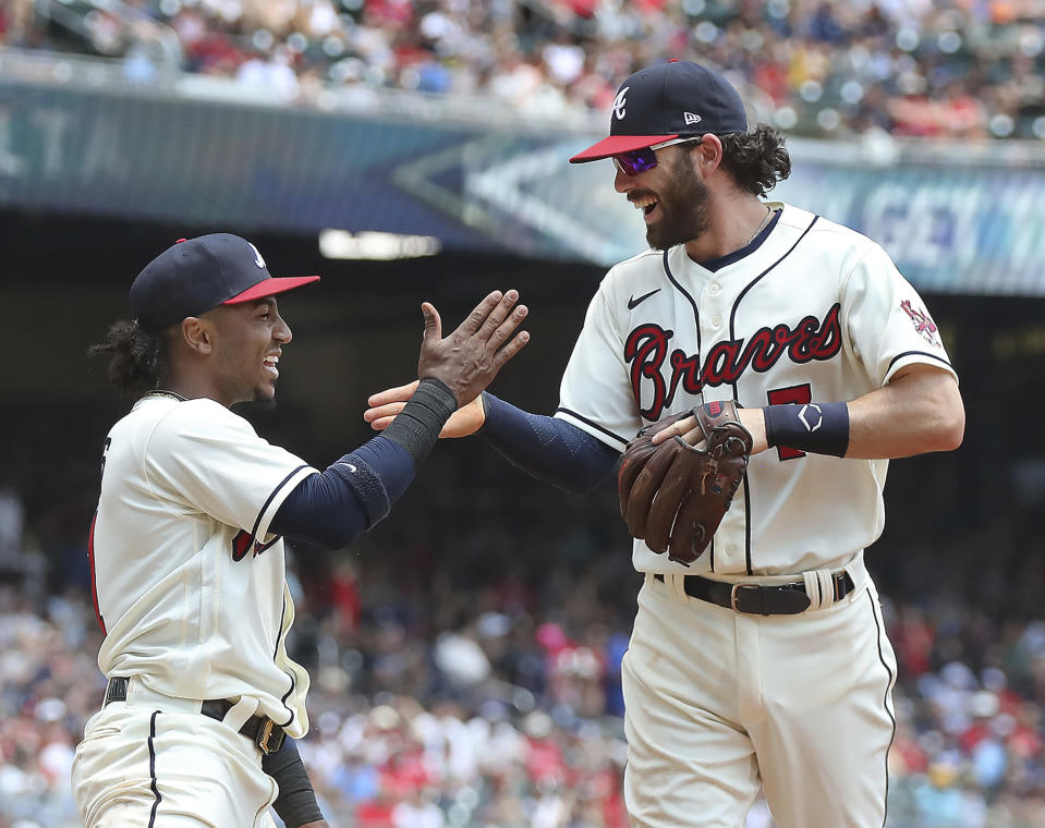 Atlanta Braves' Ozzie Albies, left, and Dansby Swanson celebrate after turning a double play against the Pittsburgh Pirates on a bunt during the second inning of a baseball game Sunday, May 23, 2021, in Atlanta. (Curtis Compton/Atlanta Journal-Constitution via AP)