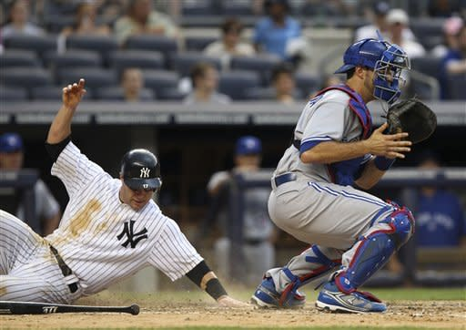 New York Yankees' Jayson Nix, left, slides safely home as Toronto Blue Jays catcher J.P. Arencibia waits for the throw during the sixth inning of a baseball game, Wednesday, July 18, 2012, at Yankee Stadium in New York. (AP Photo/Seth Wenig)