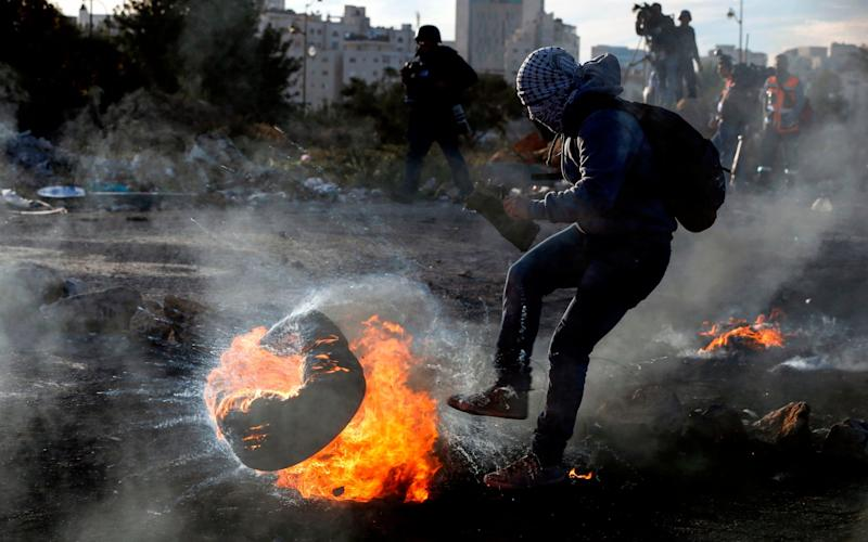A Palestinian protester kicks a flaming tire during clashes with Israeli forces in the West Bank city of Ramallah on Monday - AFP