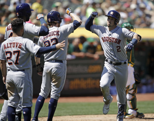 Houston Astros' Alex Bregman, right, is congratulated by Josh Reddick (22), Jose Altuve (27) and Yordan Alvarez after hitting a three run home run off Oakland Athletics' Brett Anderson in the fifth inning of a baseball game Sunday, Aug. 18, 2019, in Oakland, Calif. (AP Photo/Ben Margot)