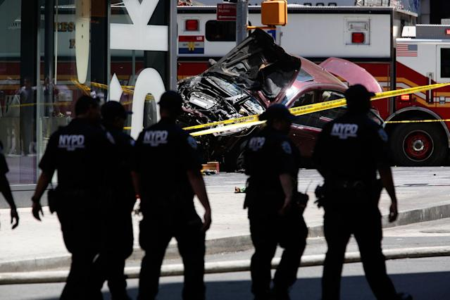 <p>Flames and smoke rises from a wrecked vehicle after it plowed into pedestrians on a busy sidewalk on the corner of West 45th St. and Broadway at Times Square, New York, NY United States on May 18, 2017. Multiple pedestrians were struck Thursday by a speeding vehicle in the heart of New York City, according to reports. (Photo: Volkan Furuncu/Anadolu Agency/Getty Images) </p>