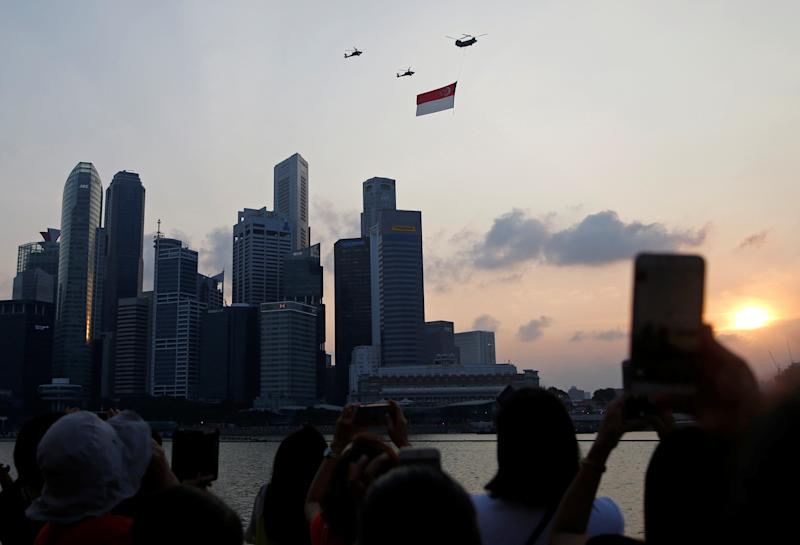 People take photos as helicopters fly past with a Singapore flag during the 54th National Day Parade in Singapore August 9, 2019. REUTERS/Feline Lim