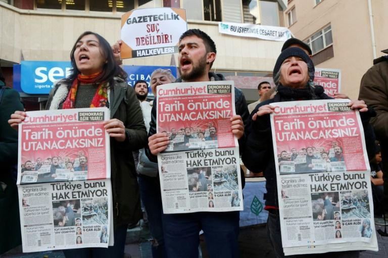 """Protesters hold copies of the Turkish daily """"Cumhuriyet"""" during a demonstration outside the newspaper's headquarters in Ankara on November 5, 2016"""