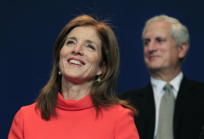 Caroline Kennedy smiles as her husband, Ed Schlossberg, sits at right during the presentation of the 2012 John F. Kennedy Profile in Courage Awards at the JFK Library in Boston, Monday, May 7, 2012. (AP Photo/Elise Amendola)