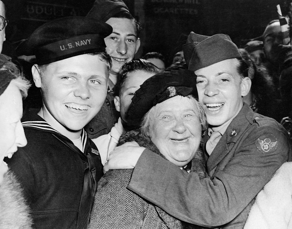 <p>English soldiers and citizens, young and old, celebrate Germany's unconditional surrender in Piccadilly Circus, London.</p>