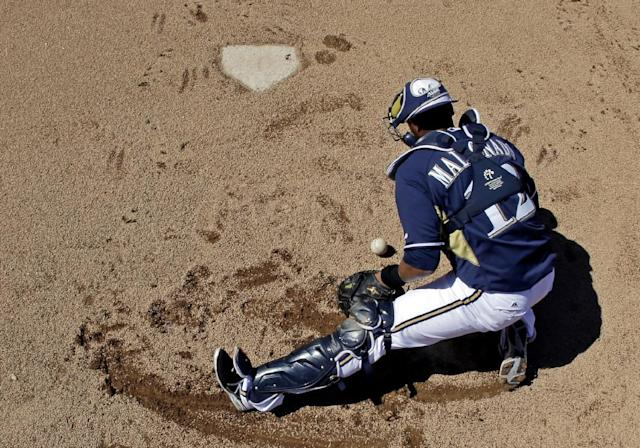 Milwaukee Brewers catcher Martin Maldonado fields a ball before an exhibition spring training baseball game against the Chicago Cubs, Monday, March 3, 2014, in Phoenix. (AP Photo/Morry Gash)