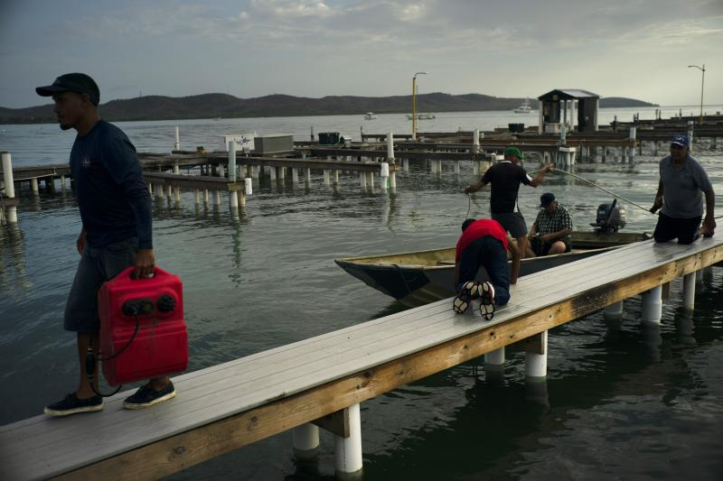 People arrive to a private harbor to move boats away for protection ahead of the arrival of Tropical Storm Dorian in Boqueron, Puerto Rico, Aug. 27, 2019. (Photo: Ramon Espinosa/AP)