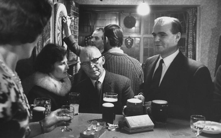 Toolmaker at leisure: Ray Willis with his wife and father-in-law at his sister's pub, 1965, from a photo-essay by Terence Spencer - Popperfoto / Getty