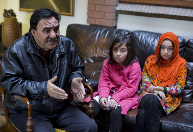 In this Nov. 29, 2018 photo, Mir Aman speaks to The Associated Press with his daughters Shahnaz, right, and Shakeela, in Islamabad, Pakistan. Scores of Pakistani men, like Aman, whose Muslim Uighur wives have disappeared into internment camps in China feel helpless, fighting a wall of silence as they struggle to reunite their families. Political and economic factors, including concerns about losing out on vast Chinese investments, have kept Muslim countries like Pakistan quiet about the plight of their fellow Muslims, being weaned off their faith in so-called re-education camps. (AP Photo/B.K. Bangash)