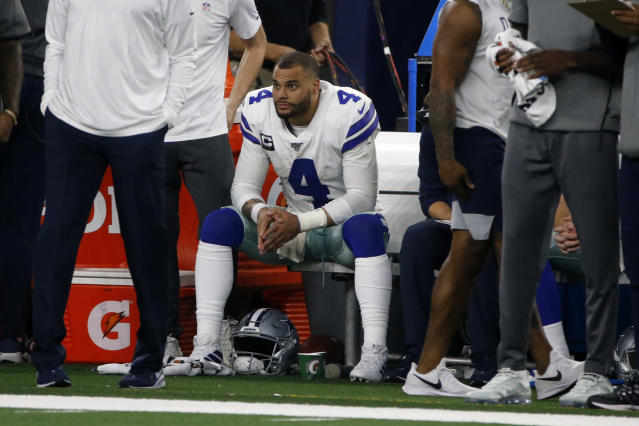 Dallas Cowboys quarterback Dak Prescott (4) sits on the bench by staff late in the second half of an NFL football game against the Buffalo Bills in Arlington, Texas, Thursday, Nov. 28, 2019. (AP Photo/Michael Ainsworth)