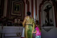 A bullfighter prays with a girl inside of a chapel before the start of a bullfight amid the coronavirus pandemic at Las Ventas bullring in Madrid, Spain, Sunday, July 4, 2021. (AP Photo/Manu Fernandez)