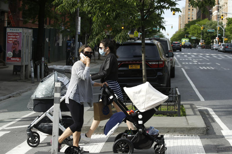 NEW YORK, NEW YORK - MAY 18: Women wearing protective masks cross the street with baby carrieges as some restrictions begin to lift during the coronavirus pandemic on May 18, 2020 in New York City. COVID-19 has spread to most countries around the world, claiming over 320,000 lives and infecting over 4.8 million people (Photo by John Lamparski/Getty Images)