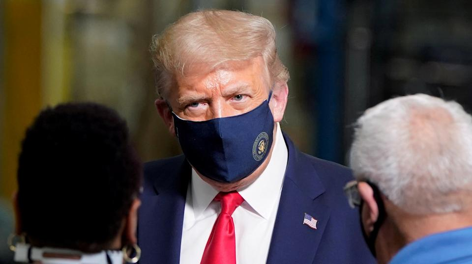 U.S. President Donald Trump wears a protective face mask due to the coronavirus disease (COVID-19) pandemic as he talks with workers while touring a Whirlpool Corporation washing machine factory in Clyde, Ohio, U.S., August 6, 2020. REUTERS/Joshua Roberts     TPX IMAGES OF THE DAY