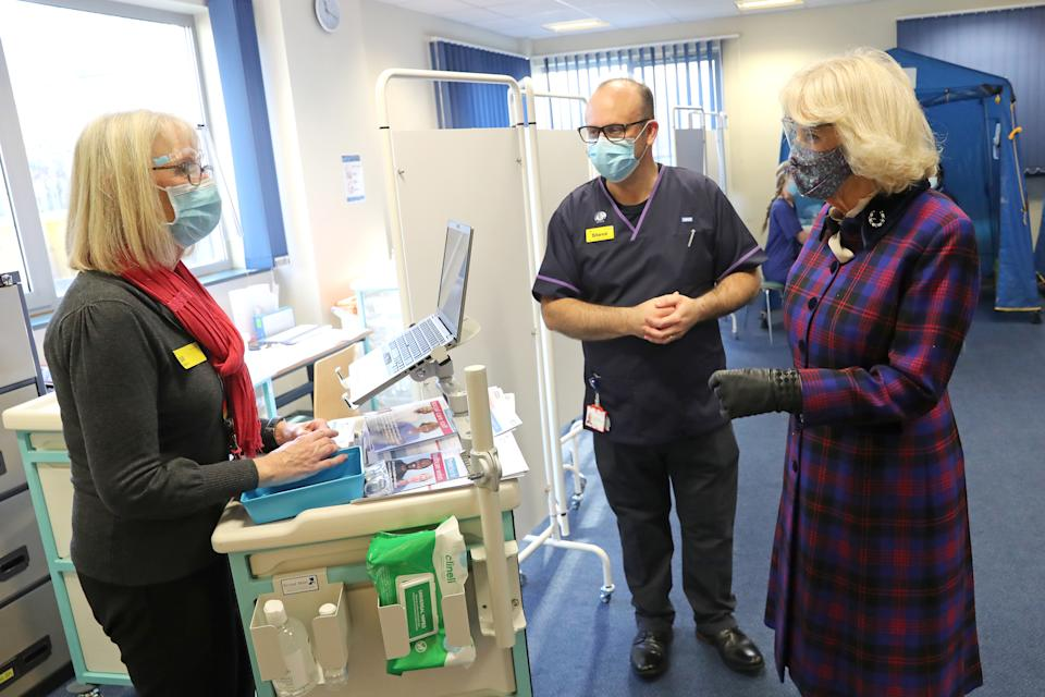 GLOUCESTER, ENGLAND - DECEMBER 17: Camilla, Duchess of Cornwall wears a face-mask and protective glasses while speaking with NHS staff involved in the vaccination programme during a visit to Gloucestershire Vaccination Centre at Gloucestershire Royal Hospital on December 17, 2020 in Gloucester, England. Gloucestershire Hospitals NHS Foundation Trust is one of the largest non-specialist Trust's in England, The Trust is the designated Management and Coordination Centre for the roll out of the COVID-19 Vaccination Programme for Gloucestershire. Their Royal Highnesses The Prince of Wales and The Duchess of Cornwall previously visited Gloucestershire Royal Hospital in June of this year, the first engagement outside of a Royal residence by any Member of the Royal Family following the first national lockdown. (Photo by Chris Jackson/Getty Images)