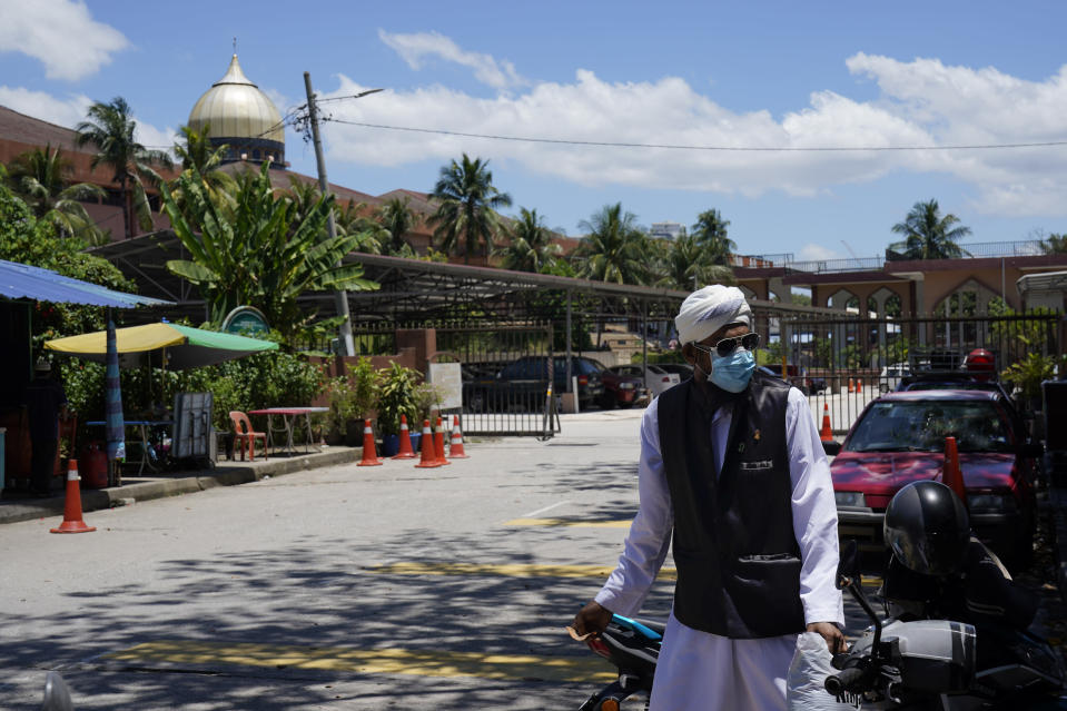 A man wears a face masks as he walks out from the Sri Petaling Mosque in Kuala Lumpur, Malaysia, on Monday, March 16, 2020. For most people, the new coronavirus causes only mild or moderate symptoms. For some it can cause more severe illness. (AP Photo/Vincent Thian)