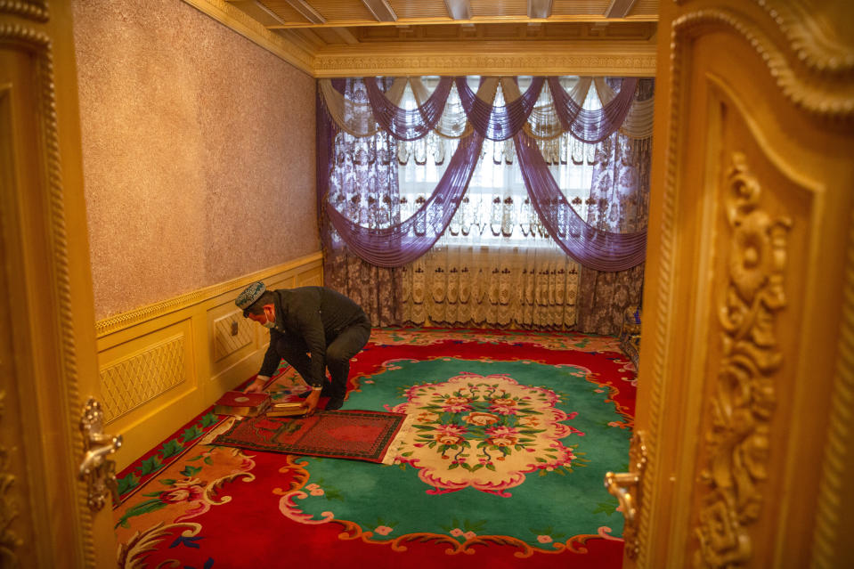 Tursunjan Mamat sets down a copy of the Quran during a government organized visit for foreign journalists to his home in Aksu in western China's Xinjiang Uyghur Autonomous Region on April 20, 2021. Under the weight of official policies, the future of Islam appears precarious in Xinjiang, a remote region facing Central Asia in China's northwest corner. Outside observers say scores of mosques have been demolished, which Beijing denies, and locals say the number of worshippers is on the decline. (AP Photo/Mark Schiefelbein)