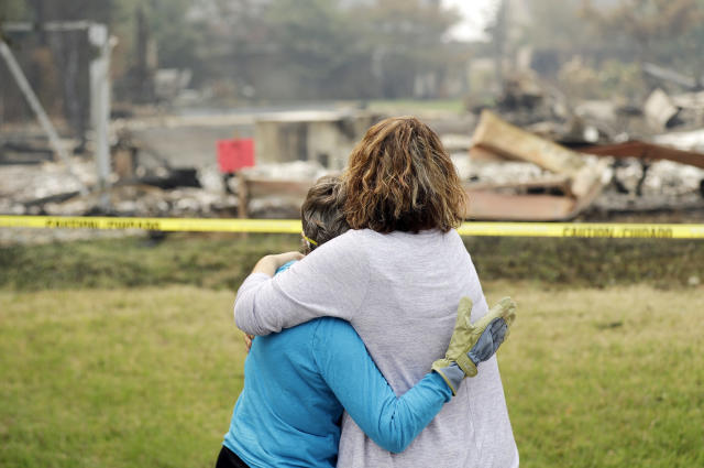 <p>Carol Smith, left, gets a hug from her daughter Suzie Scatena, after seeing her fire-ravaged home for the first time Thursday, Aug. 2, 2018, in Redding, Calif. (Photo: Marcio Jose Sanchez/AP) </p>