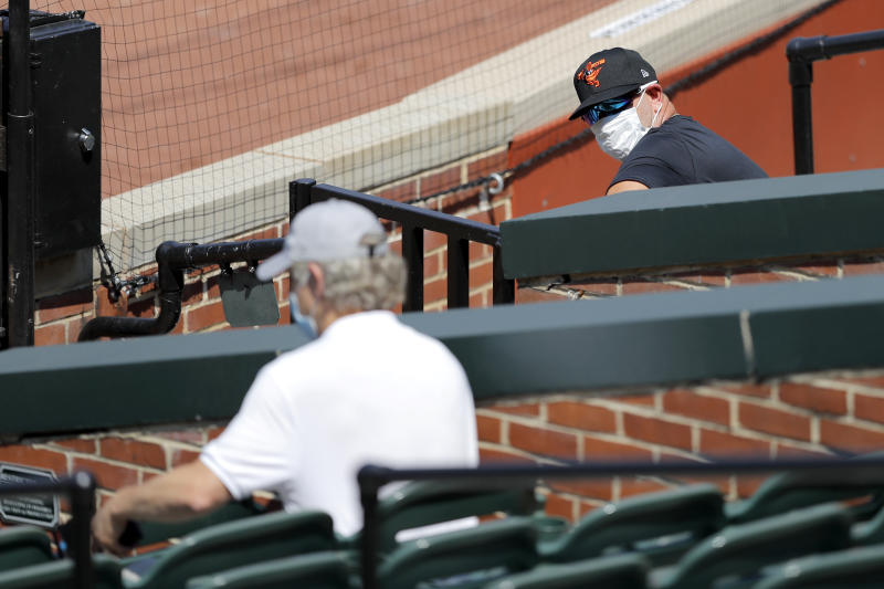 Baltimore Orioles manager Brandon Hyde, right, wears a face mask to protect against the coronavirus as he talks with general manager Mike Elias during baseball training camp, Friday, July 3, 2020, in Baltimore. (AP Photo/Julio Cortez)
