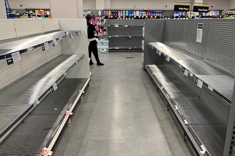 A customer walks past two empty shelves in Woolworths.
