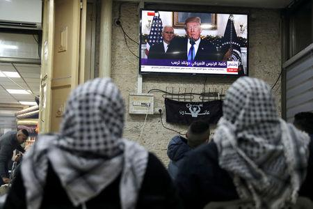 Palestinians watch a televised broadcast of U.S. President Donald Trump delivering an address where he is expected to announce that the United States recognises Jerusalem as the capital of Israel, in Jerusalem's Old City December 6, 2017. REUTERS/Ammar Awad